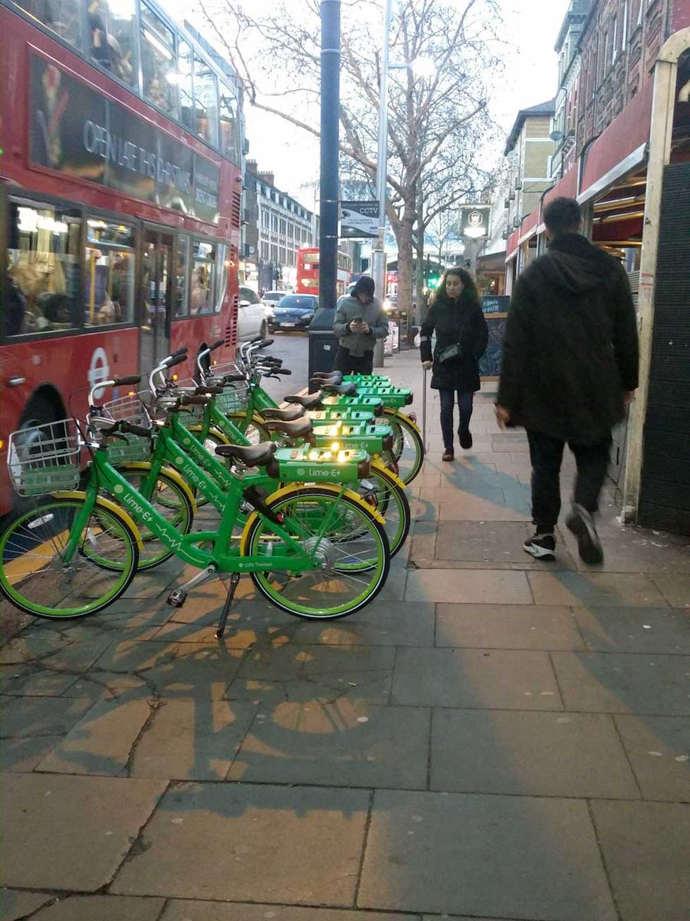 Row of LimeBikes on a pavement in kilburn, London